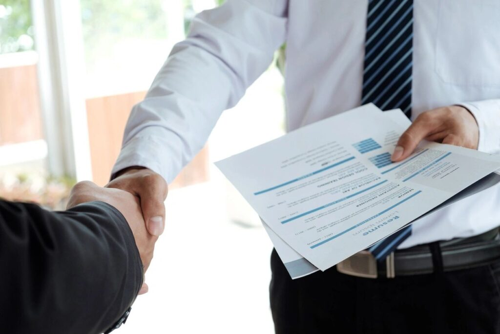 Man Holding Resume and Shaking Hand with Manager